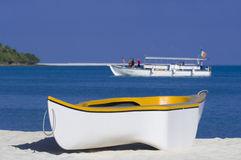 Rowing boat on sandy beach. Rowing boat moored on white sandy beach with ship in background, Maldives royalty free stock images