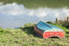 Rowing boat on the shore of Lake Weissensee. Backwards stored plastic rowing boat on the shore of Lake Weissensee near the town Füssen in Bavaria Stock Photography
