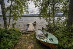 Rowing boat and wooden bench in Rantasalmi, Lakes District, Finland. Europe Stock Photo