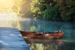 Rowing boat at wooden pier. In foggy morning stock photos
