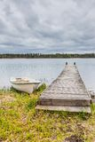 Rowing Boat and Wooden Pier. White Rowing boat Next to a Wodden Pier with a Cloudy Sky as Background Royalty Free Stock Photography