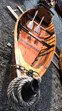 Rowing boat. A wooden rowing boat with rope bow with two oars beached at the side of a lake Stock Photo