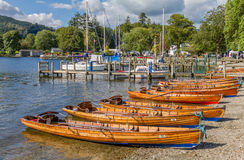 Rowing boats in Ambleside on Lake Windermere, Cumbria. Ambleside, United Kingdom - September 7, 2015: Afternoon shot of wooden rowing boats on shore of Lake Royalty Free Stock Photos