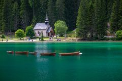 Rowing boats at Braies lake with a church in background royalty free stock photos