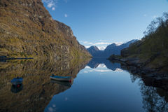 Rowing boats in the fiord of Aurland, Flam, Norway. The picturesque Aurlandsfjord with rowing boats and reflections, Flam, Norway Stock Photo