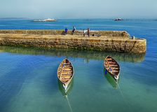 Rowing boats beside harbour Stock Photography