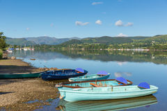 Rowing boats for hire for pleasure and leisure by beautiful lake and mountains on calm still day Royalty Free Stock Images
