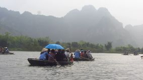 Traditional Rowing Boats Between Karst Mountains. Rowing boats between the karst mountains and rice field in Tam Coc / Trang An, Ninh Binh, Vietnam stock footage