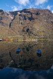 Rowing boats on mountain reflected in water Stock Photo