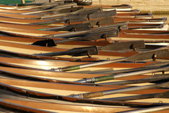 Rowing boats and oars. Rows of aligned wooden rowing boats and oars receding into background Royalty Free Stock Photos