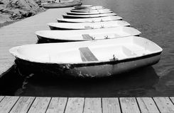 Rowing boats and pier. Black and white view of similar rowing boats moored at wooden pier Royalty Free Stock Photography