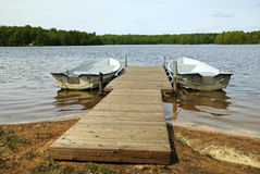 Rowing boats ready for ride. Two rowing boats moored to wooden bridge on Swedish lake Stock Photography