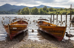 Rowing boats on shore of Derwent Water, Keswick. Stock Photos