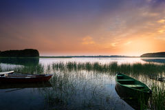 Rowing boats on sunset. Rowing boat floating on the calm depths of the Lake Lasmiady. Just the sun rises. Masuria, Poland stock images