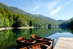 Rowing boats tied to pontoon on lake in Montenegro Stock Images