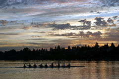 Rowing de la gente en la salida del sol Fotos de archivo