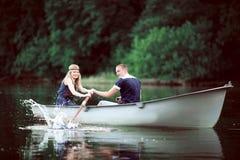 Rowing de la muchacha y del individuo en el lago Imagen de archivo libre de regalías