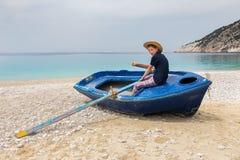 Rowing del adolescente en barco en la playa griega Foto de archivo