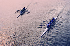 Rowing duet. Two skiffs of four rowers competing in a sunrise light Royalty Free Stock Photography