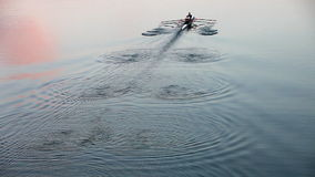 Rowing at dusk - leaving wonderful waving pattern stock footage