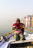 Rowing on the Ganges. In the early morning a fisherman is rowing on the Ganges. In the background are the ghats of Varanasi Royalty Free Stock Image