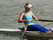 Rowing girl. Sporty young lady rowing in boat on water Stock Image
