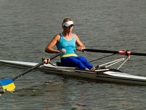 Rowing girl. Sporty young lady rowing in boat on water Royalty Free Stock Photography