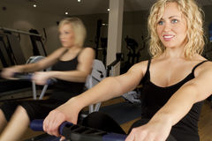 Rowing At The Gym. Two beautiful young women using rowing machines at the gym. The girl in the background is shown moving using in-camera motion blur Royalty Free Stock Photos
