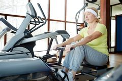 Rowing in gym. Aged female in activewear exercising on rowing machine in fitness center at leisure stock images