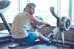 Rowing at gym. Side view of young man in sportswear doing rowing in front of window at gym and looking away stock image