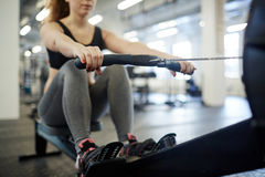 Rowing in gym. Young woman training on rowing-machine in gym stock image