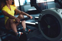 Rowing in the gym. Young woman training using rowing machine Stock Image