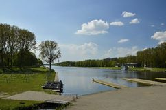 The rowing lake in the Amsterdam Forest. Amsterdam, Netherlands - May 7, 2016: The olympic rowing lake (Bosbaan) and the service building, in the forest ( Royalty Free Stock Photo