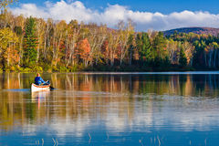 Rowing in New England Fall Colors. A man rowing a boat on Spectable Pond, Vermont, in brilliant fall colors royalty free stock photo