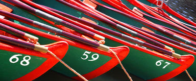Rowing by numbers. Brigtly, contrasting coloured rowing boats tethered on the river side that are numbered Stock Photos