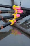 Rowing oars. Rowing boat oars stacked on the shore. Four oars and a sweep oar for surf rowing boat Royalty Free Stock Image