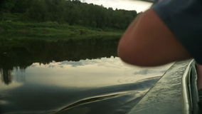 Rowing a paddle in the calm water of the river. stock video
