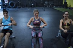 Rowing people at gym smiling and having fun Royalty Free Stock Photography