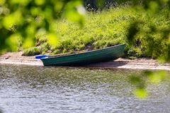 Rowing pleasure boat with oars near the shore. Empty green wooden rowboat near the shore on a sunny summer day. rowing pleasure boat with oars near the shore stock photography