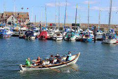 Rowing skiff Anstruther in harbour Anstruther. View of a traditional coastal rowing skiff being rowed in the harbour at Anstruther in the Kingdom of Fife Royalty Free Stock Images