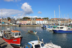 Rowing skiff and other boats harbour Anstruther. View of a traditional coastal rowing skiff being rowed in the harbour at Anstruther in the Kingdom of Fife Stock Photography