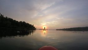 Rowing on a SUP board. SUP board on the background of the sun. Sunrise. A man is rowing on a SUP board at dawn of the sun. Reflection of the sky and clouds on stock footage