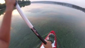 Rowing on a SUP board. Of the first person. The camera is on a paddle. Rowing on a SUP board. SUP board on the background of the sun. Sunrise.   Of the first stock video footage