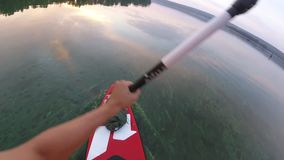 Rowing on a SUP board. Of the first person. The camera is on a paddle. Rowing on a SUP board. SUP board on the background of the sun. Sunrise.   Of the first stock footage