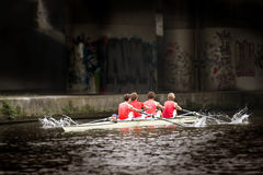 Rowing team. Top sport rowing team (coxed four) emerging from the dark of a viaduct, at a high pace, splashes of water coming from the oars Stock Image