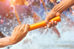 Rowing team. Hands passing a relay baton on rowing team background and color tone effect Royalty Free Stock Photos