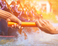 Rowing team race and color tone effect. Hands passing a relay baton on rowing team background and color tone effect royalty free stock photos