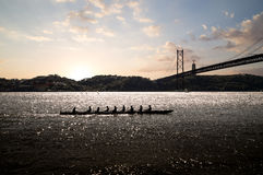 Rowing team at sunset. Silhouette of people on rowing boat on the sea with suspension bridge in the background at sunset. Lisbon, Portugal royalty free stock image