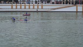 Rowing team is training in city river. Professional rowing team pass by camera on boat or kayak during training in preparation for tournament or competition race stock video footage