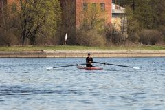 Rowing training - rower on the boat. St. Petersburg, Russia - April 26, 2019: young man rowing a single scull. rowing training on the Malaya Nevka river stock image